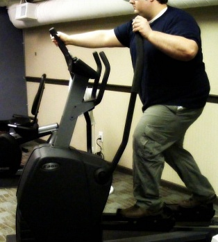 Image of a man using an elliptical exercise machine.